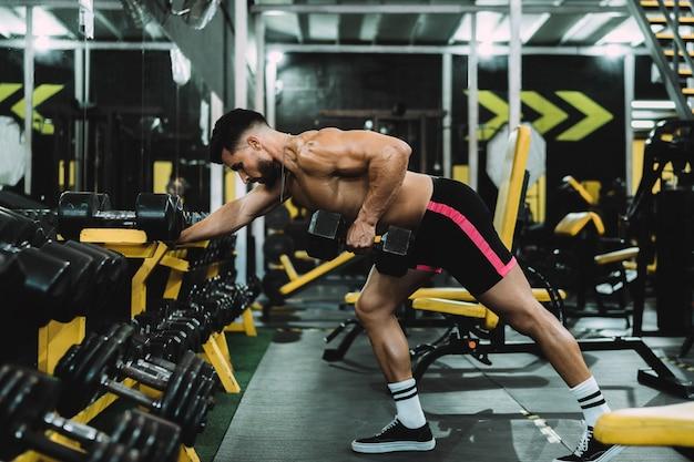 Mężczyzna ćwiczący z hantlami w sali gimnastycznej
