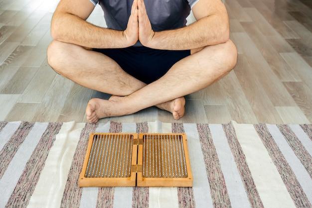 Mężczyzna ćwiczeń jogi medytacji siedząc złączonymi rękami na podłodze w pobliżu tablicy sadhu