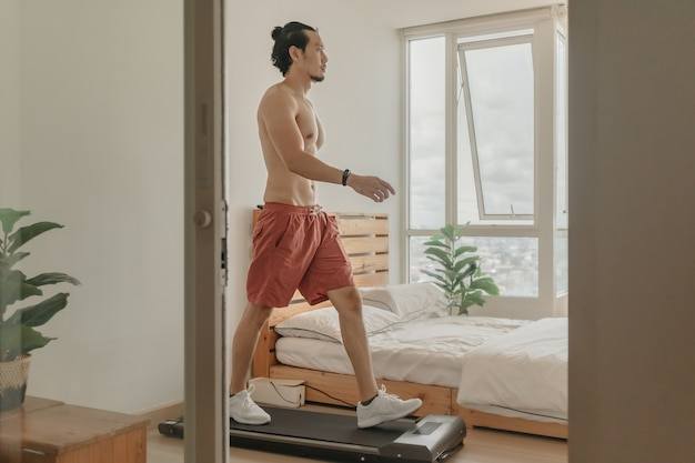 Mężczyzna ćwiczy, chodząc po bieżni w swoim mieszkaniu