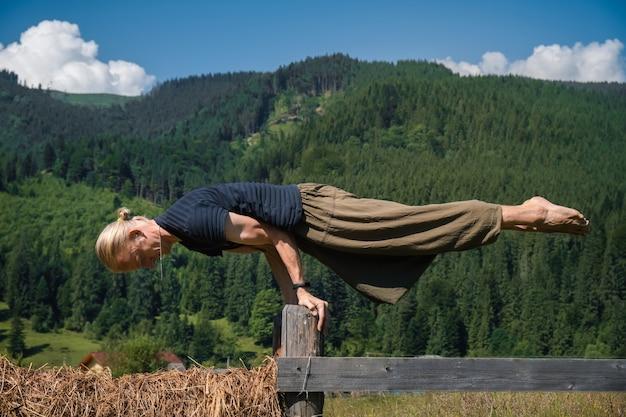 Mężczyzna ćwiczy ćwiczenia jogi w słoneczny dzień w górach
