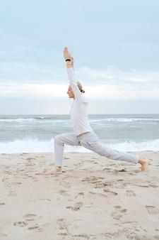 Mężczyzna ćwiczy jogę na plaży dla dorosłych ćwiczy jogę na plaży