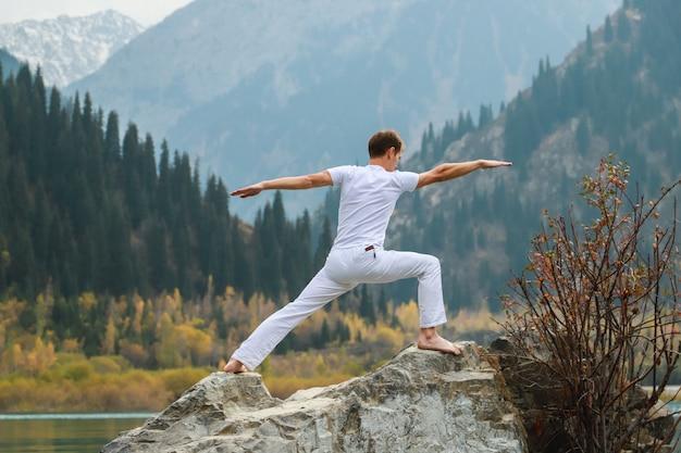 Mężczyzna ćwiczy jogę na tle gór. ustaw virabhadrasanę 2 lub wojownika.