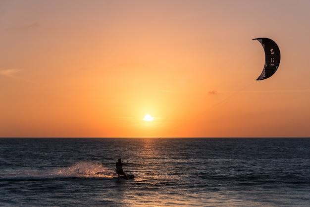 Mężczyzna ćwiczy kania surfing przy zmierzchem w plaży hiszpania