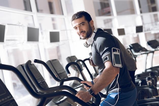 Mężczyzna ćwiczy na bieżni w nowoczesnej siłowni.