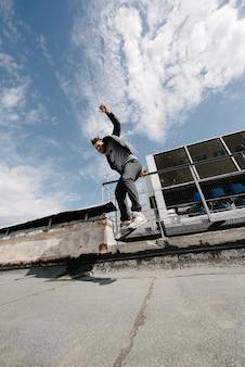 Mężczyzna ćwiczy parkour, biegnie i skacze przez przeszkody