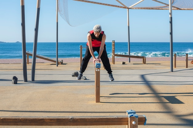 Mężczyzna ćwiczy sport w plenerowym drewnianym miastowym gym blisko morza.