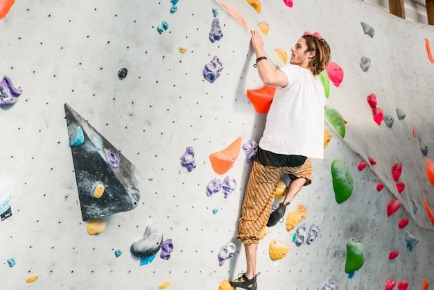 Mężczyzna ćwiczy wspinaczkowy skałę na sztucznej ścianie