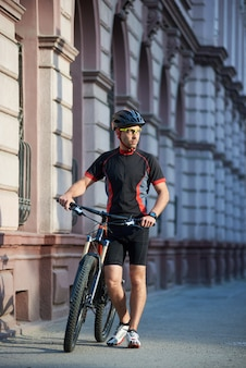 Mężczyzna cyklista stoi blisko rowerowego główkowania o przyszłościowym sukcesie