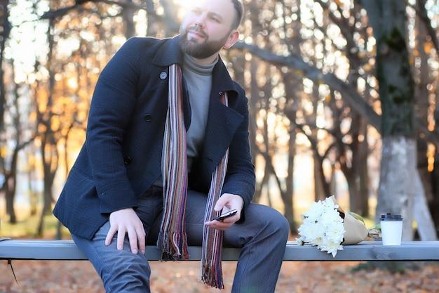 Mężczyzna czeka na ławce randka w jesiennym parku z kwiatem
