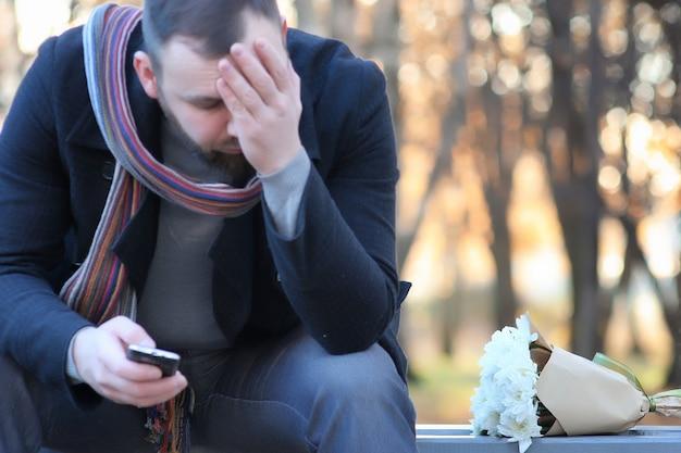 Mężczyzna czeka na ławce randkę w jesiennym parku z kwiatem