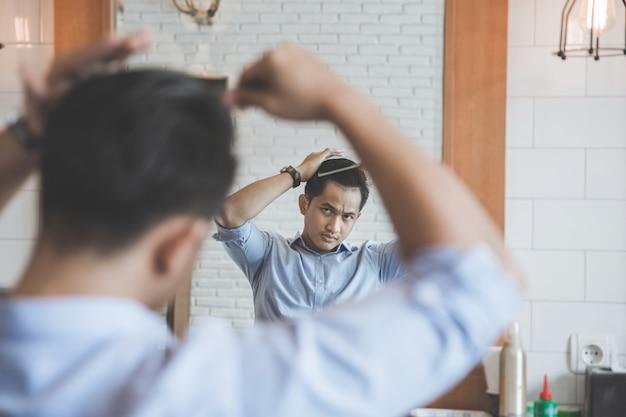 Mężczyzna czesanie włosów po obcięciu w zakładzie fryzjerskim