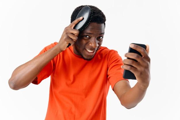 Mężczyzna czesząc głowę telefon afrykański wygląd w dłoni