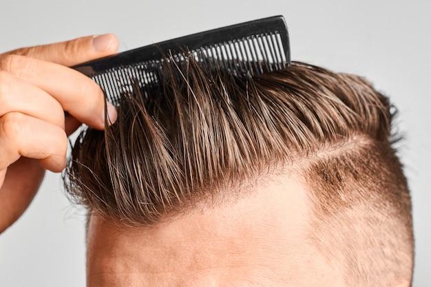 Mężczyzna czesze swoje czyste włosy plastikowym grzebieniem. stylizacja włosów w domu. pojęcie wypadania włosów lub łupieżu