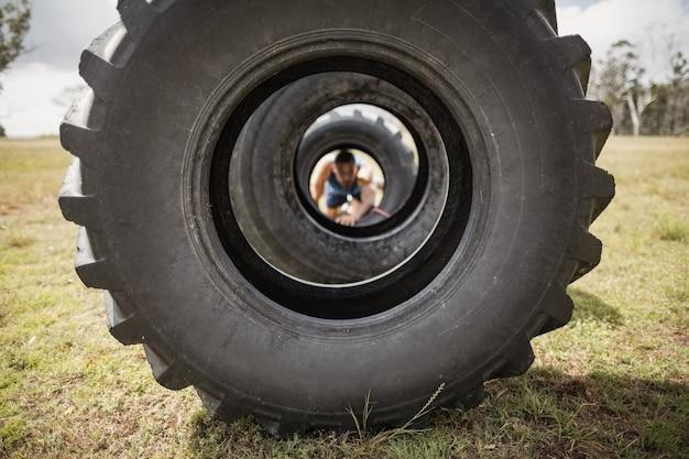 Mężczyzna czołgający się przez oponę podczas toru przeszkód w obozie treningowym