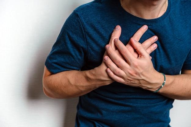 Mężczyzna czuje ból w żołądku ściskając bolesne miejsce na białej ścianie
