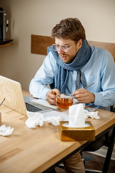 Mężczyzna czuje się chory i zmęczony. mężczyzna z kubkiem pracuje w domu, biznesmen przeziębiony, grypa sezonowa.
