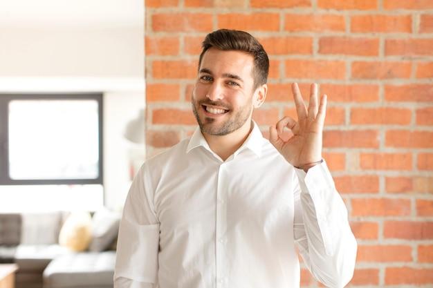 Mężczyzna czuje się szczęśliwy, zrelaksowany i usatysfakcjonowany, okazuje aprobatę dobrym gestem, uśmiecha się