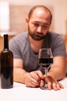 Mężczyzna czuje się wykończony i przygnębiony emocjonalnie po wypiciu kieliszka czerwonego wina. choroba nieszczęśliwa i lęk, uczucie wyczerpania z powodu problemów z alkoholizmem.