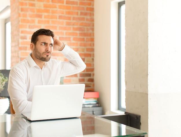 Mężczyzna czuje się zdezorientowany i zdezorientowany, drapiąc się po głowie i patrząc w bok