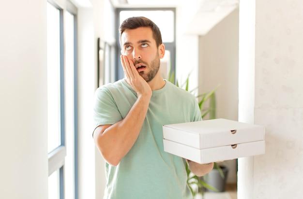 Mężczyzna czuje się znudzony, sfrustrowany i senny po męczącym, nudnym i żmudnym zadaniu, trzymając twarz dłonią