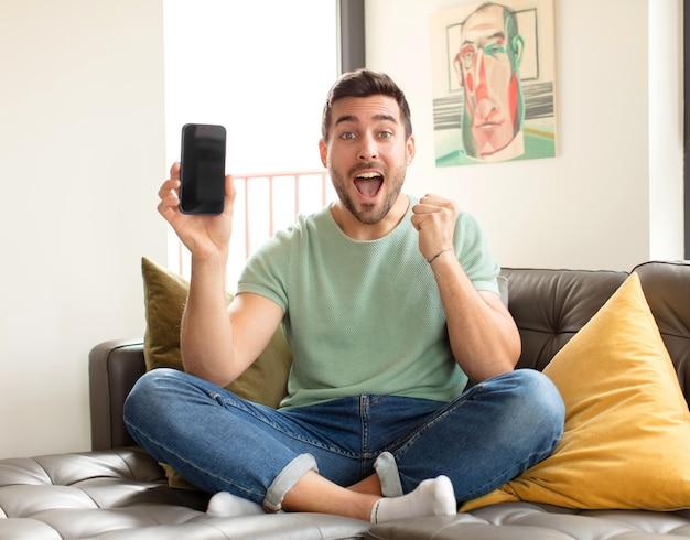 Mężczyzna czuje się zszokowany, podekscytowany i szczęśliwy, śmieje się i świętuje sukces, mówiąc wow!