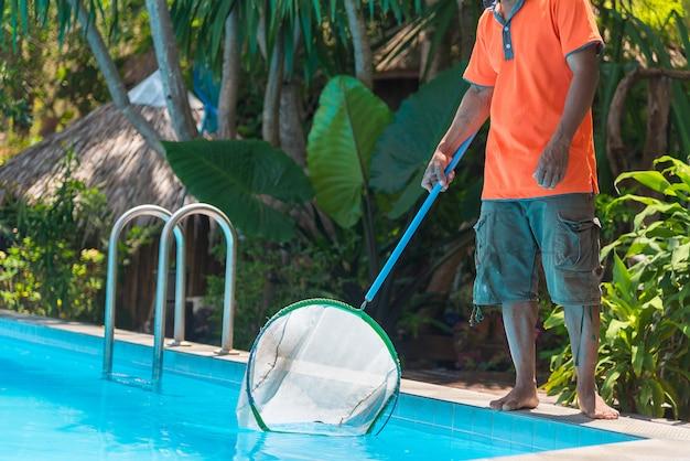 Mężczyzna czyści błękitnego pływackiego basen od liści z cleaning siatką.