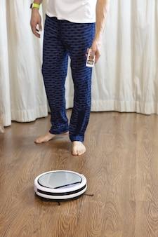Mężczyzna czyści dom, włącza bezprzewodowy odkurzacz robota za pomocą pilota