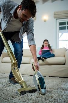 Mężczyzna czyści dywan odkurzaczem