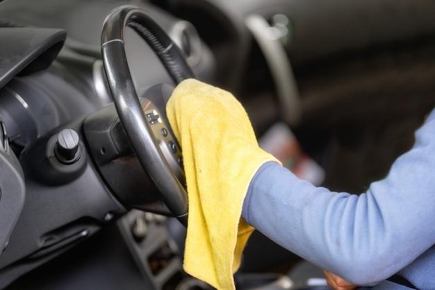 Mężczyzna czyści kierownicę z żółtą ściereczką z mikrofibry.