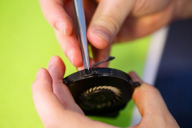 Mężczyzna czyści laptopa specjalnym narzędziem z kurzu. naprawa i konserwacja laptopów i komputerów pc usługi reklamowe w zakresie naprawy elektroniki i urządzeń.