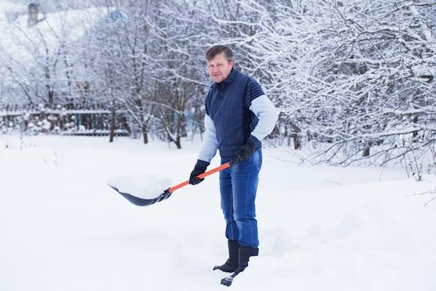 Mężczyzna czyści łopatę do śniegu