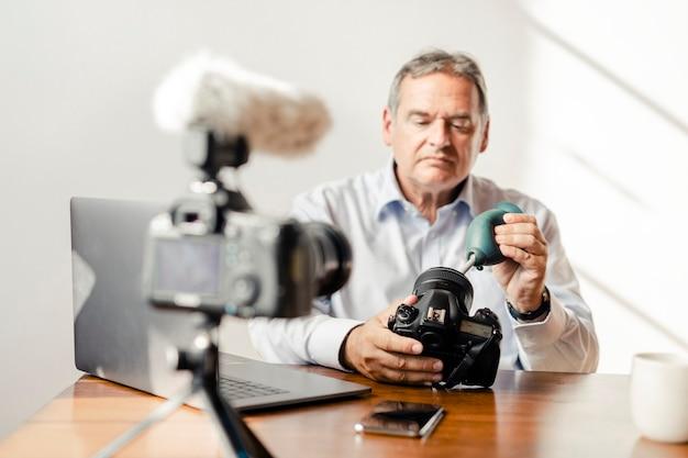 Mężczyzna czyści obiektyw aparatu gumową dmuchawą