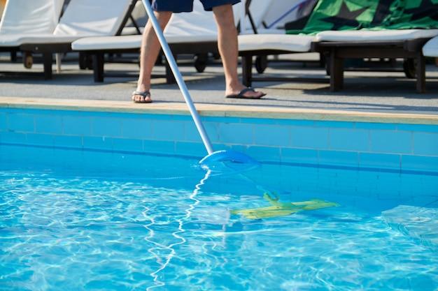 Mężczyzna czyści odkryty basen z podwodną rurą próżniową