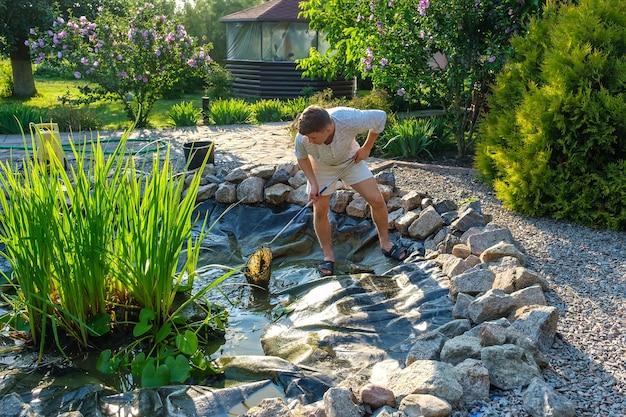 Mężczyzna czyści podbierak do stawu ogrodowego z błota i roślin wodnych