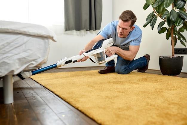 Mężczyzna czyści podłogę za pomocą odkurzacza w nowoczesnej koncepcji białego salonu łatwego czyszczenia za pomocą nowoczesnego nowego odkurzacza