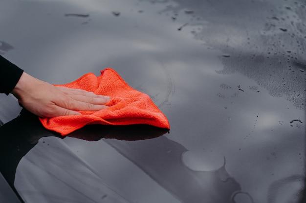 Mężczyzna czyści powierzchnię samochodu ściereczką z mikrofibry