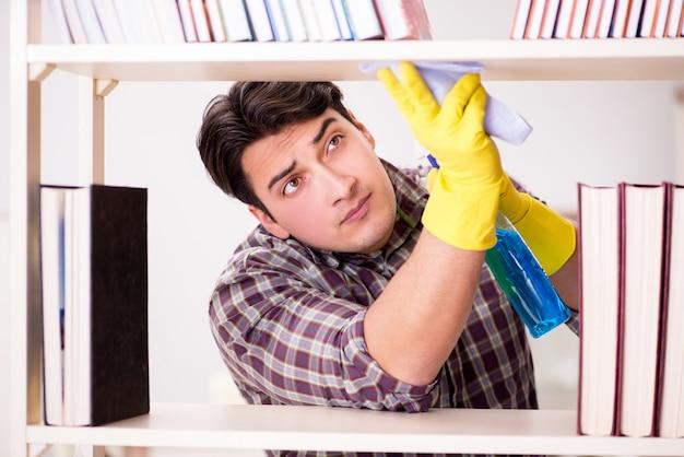 Mężczyzna czyści pył z półki na książki