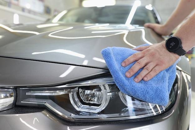 Mężczyzna czyści samochód za pomocą koncepcji usług myjni samochodowej z mikrofibry