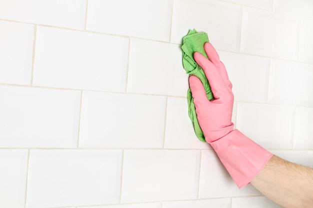 Mężczyzna czyści ścianę z białych płytek metra gąbką
