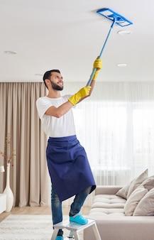 Mężczyzna czyści sufit i lampy w salonie. koncepcja usługi sprzątania domu.