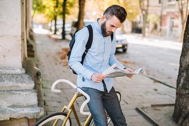 Mężczyzna czyta gazetę blisko bicyklu