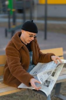 Mężczyzna czyta gazetę i pali na ławce na ulicy