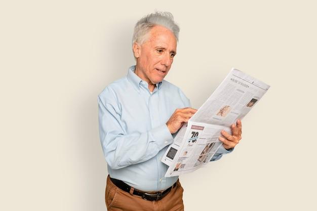 Mężczyzna czyta gazetę na beżowym tle