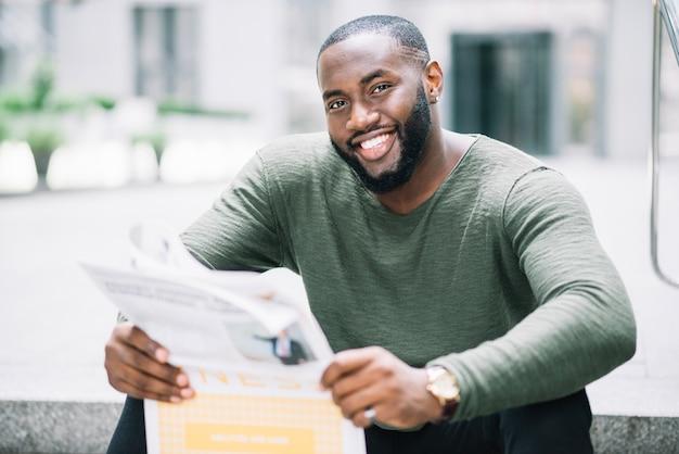 Mężczyzna czyta gazetę na schodach