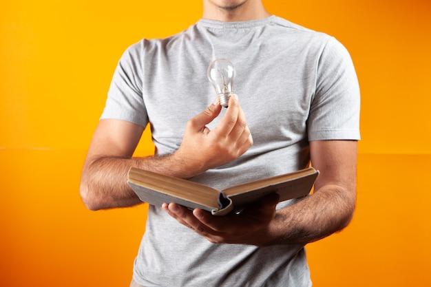 Mężczyzna czyta książkę i trzyma żarówkę. pomysł koncepcyjny z książki o pomarańczowym biurze