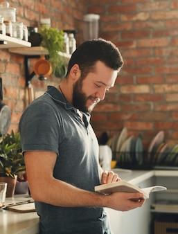 Mężczyzna czyta książkę kucharską w kuchni
