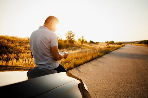 Mężczyzna czyta książkę siedzi na masce samochodu