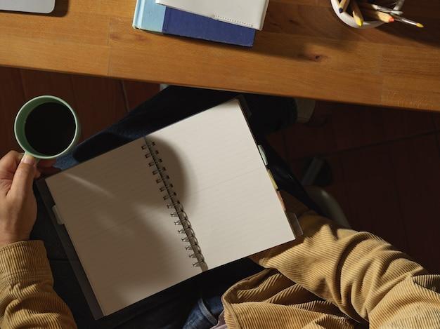 Mężczyzna czyta książkę trzymając filiżankę kawy w miejscu pracy