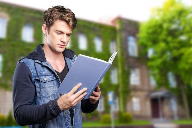 Mężczyzna czyta książkę w jego rękach