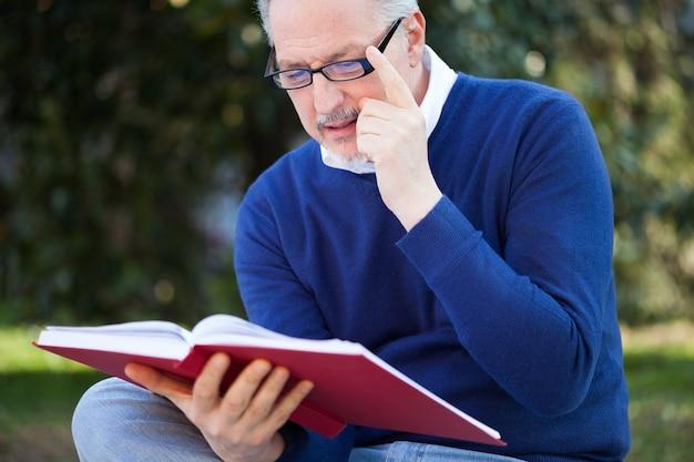 Mężczyzna czyta książkę w parku